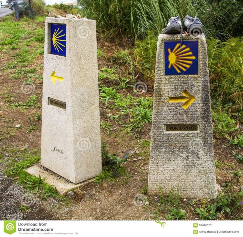 richtingtekens-kammosselshell-en-gele-pijl-met-blauwe-achtergrond-op-een-muur-camino-de-santiago-spanje-107022025